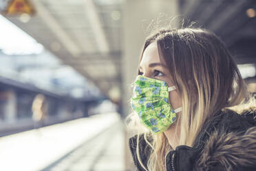 Portrait of young woman wearing mask at station platform - BFRF02206