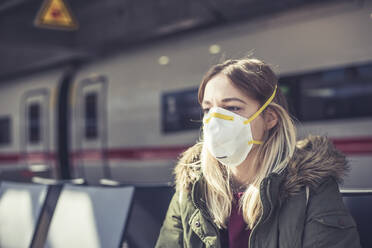 Portrait of young woman wearing respirator mask at station platform - BFRF02209