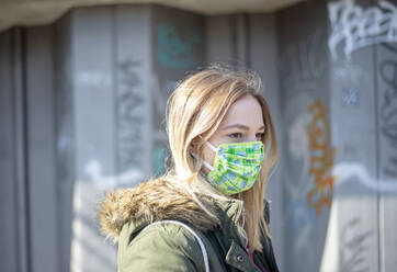 Portrait of young woman wearing mask in the city - BFRF02212