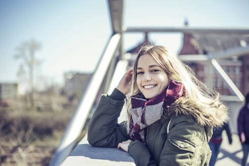 Portrait of smiling young woman on a bridge in the city - BFRF02215