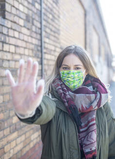 Portrait of young woman wearing mask raising her hand - BFRF02218