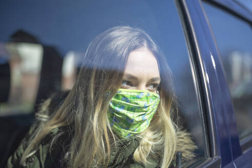 Portrait of young woman wearing mask in car - BFRF02221