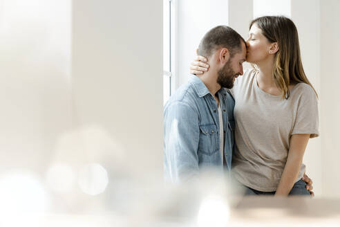 Affectionate couple in love at window in their home - SBOF02161