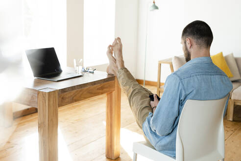 Young man at home typing on his smartphone in modern living room with his feet on the table - SBOF02215