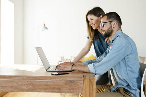 Smiling couple working at laptop from home in home office in modern living room - SBOF02218