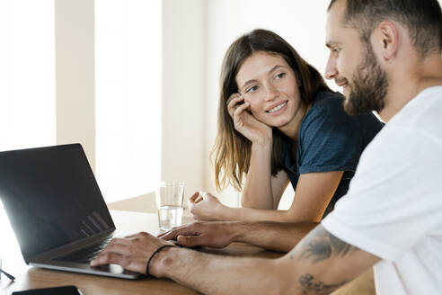 Smiling couple working at laptop from home in home office - SBOF02221
