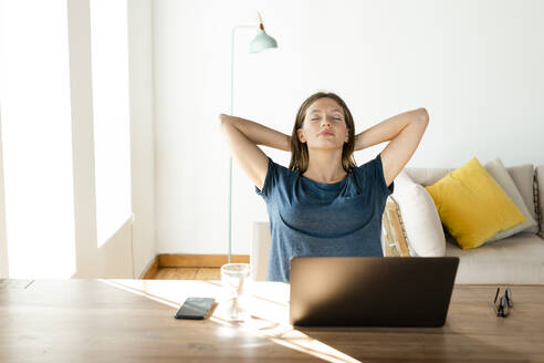 Young woman at home relaxing and having a break from working at laptop in home office - SBOF02227