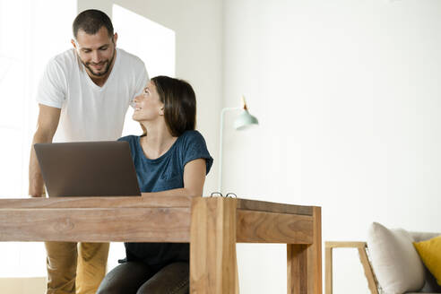 Smiling couple working at laptop from home in home office in modern living room - SBOF02233