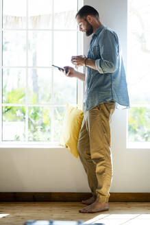 Young man at home standing at window and checking his smartphone - SBOF02275