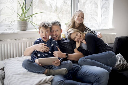 Portrait of playful family on couch at home - HMEF00843