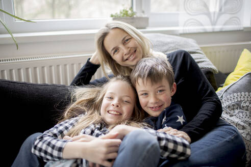 Portrait of happy mother with kids relaxing on couch at home - HMEF00846