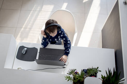 Top view of boy sitting at desk at home wearing headphones and using laptop - HMEF00855