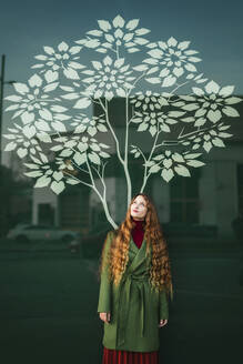 Portrait of redheaded young woman wearing green coat standing in front of glass pane with stylised tree - TCEF00338