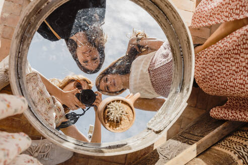 Morocco, Three young women taking mirror selfie during holiday trip - AFVF05936