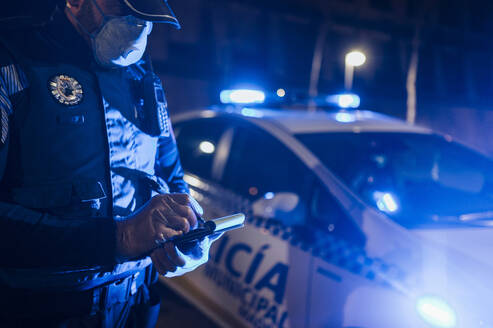 Policeman during emergency mission at night, taking notes, wearing protective gloves and mask - JCMF00524