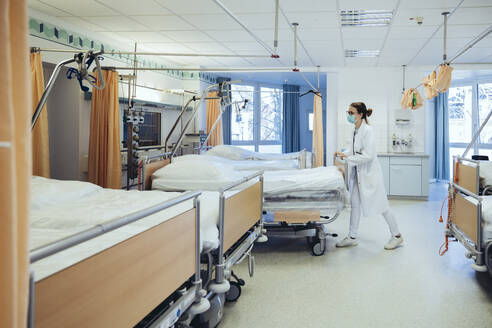 Doctor in hospital room pushing beds - MFF05242