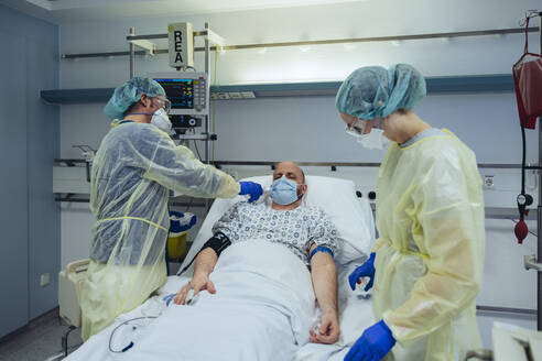 Doctors caring for patient in emergency care unit of a hospital taking temperature - MFF05305