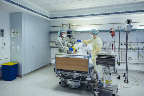 Doctors caring for patient in emergency care unit of a hospital taking blood sample - MFF05317