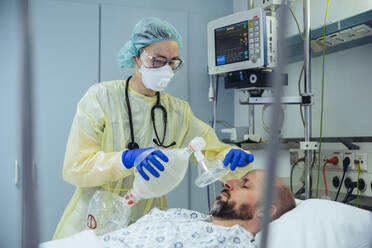 Doctor with bag valve mask caring for patient in emergency care unit of a hospital - MFF05329