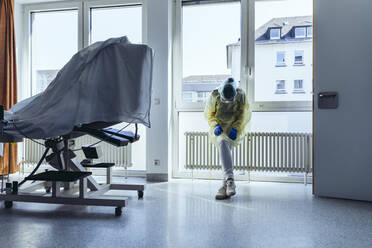 Exhausted doctor wearing personal protective equipment in hospital - MFF05356