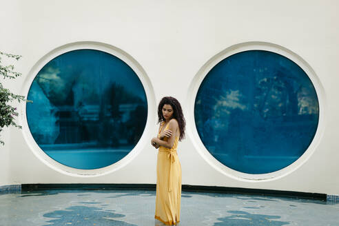 Young woman wearing yellow summer dress standing in pool - TCEF00373