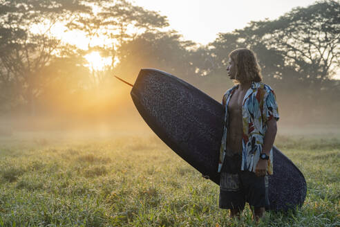 Young man with surfboard standing on a meadow at sunrise, Costa Rica - AMUF00029