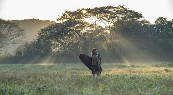 Young surfer on the way to the beach at sunrise, Costa Rica - AMUF00032