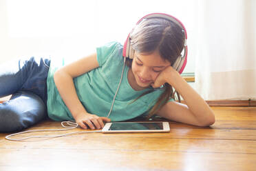 Girl lying on the floor at home using headphones and digital tablet - LVF08729