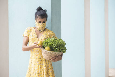 Woman wearing mouth cloth holding basket with salad and fresh fruits - AMUF00037
