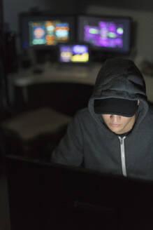 Hacker in hoody at computer in dark room - CAIF24951