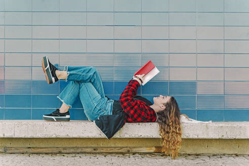 Teenage girl reading book outdoors - ERRF02964