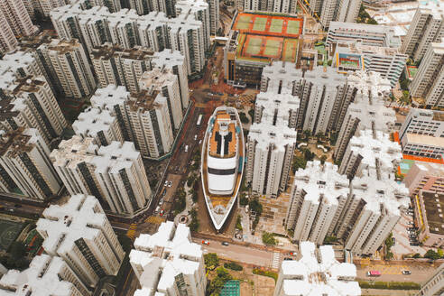 Aerial view of a boat shopping mall with symmetrical apartment blocks in WanChai, Hong Kong. - AAEF07742