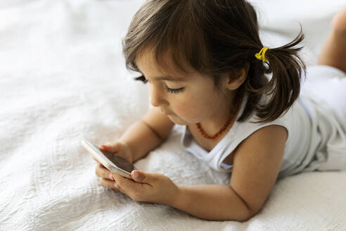 Little girl in underwear lying on bed  looking at smartphone - VABF02724