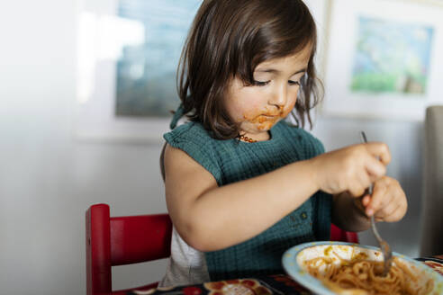 Portrait of little girl with smeared face eating pasta - VABF02730