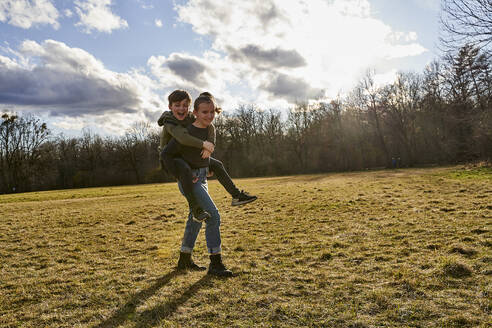 Happy girl carrying brother piggyback on a meadow - AUF00271