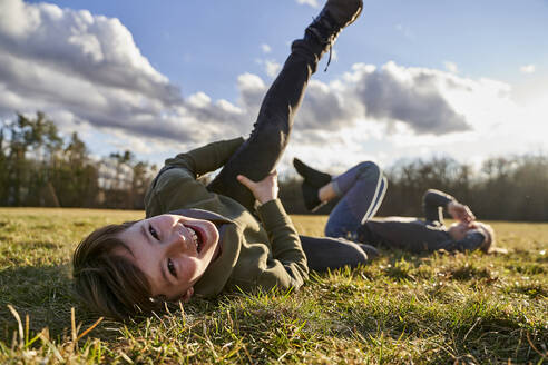 Portrait of happy boy with sister lying on a meadow - AUF00280