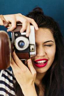 Portrait of young woman with red lips taking picture of viewer with camera - LSF00092
