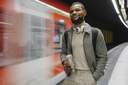 Stylish man with reusable cup and headphones in a metro station - AHSF02119