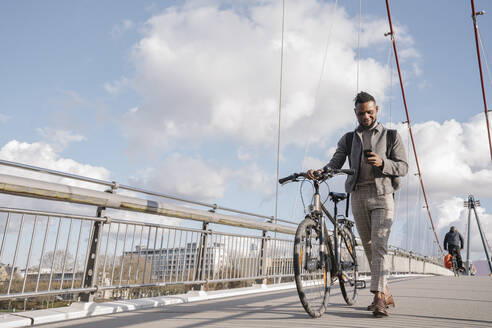 Stylish man with a bicycle using smartphone while walking on a bridge - AHSF02152