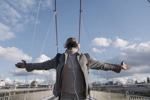 Stylish man on a bridge with headphones listening to music with outstretched arms - AHSF02158