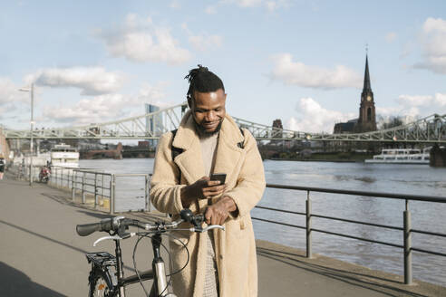 Stylish man with a bicycle using smartphone on riverbank, Frankfurt, Germany - AHSF02164