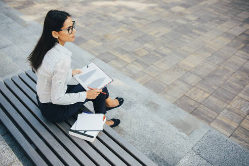 Businesswoman with clipboard sitting on a bench in a park - OYF00113