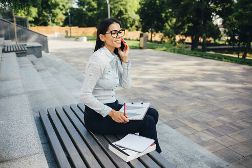 Businesswoman calling and sitting on a bench in a park - OYF00116