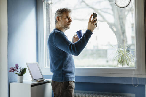 Mature man with coffee mug standing in living room taking selfie with smartphone - MCVF00249