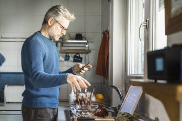 Mature man standing in his kitchen looking at smartphone while preparing salad - MCVF00258