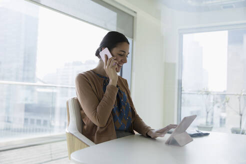 Smiling businesswoman talking on smart phone and using digital tablet in office - CAIF25626