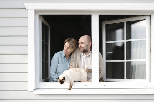 Couple with cat leaning out of window of their house - VYF00115
