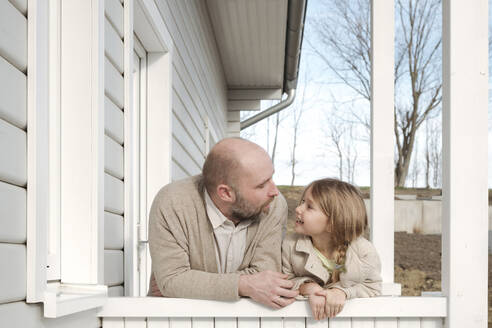 Father and his smiling daughter on porch of their house - VYF00124