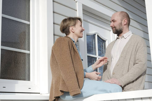 Happy couple talking on porch of their house - VYF00127