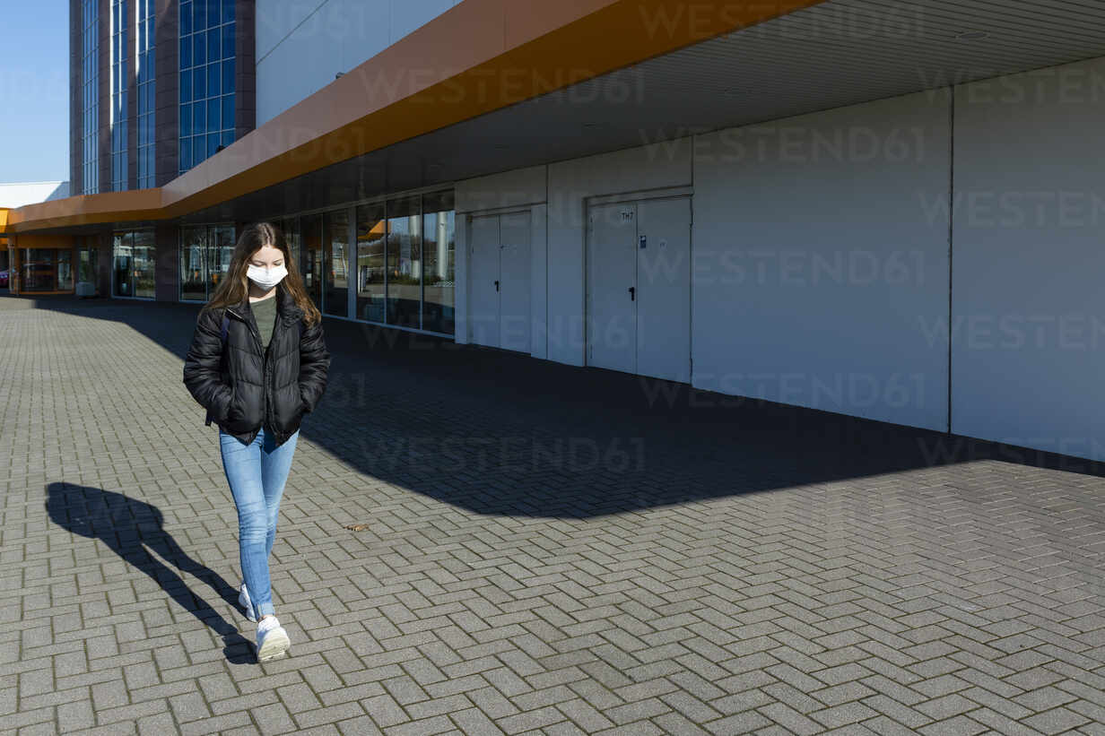 Girl with mask walking outside at closed shopping center - OJF00364 - Julia Otto/Westend61